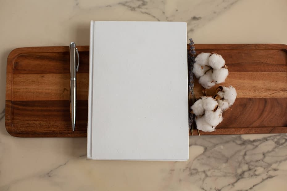 white notebook with pen and cotton flowers on tray