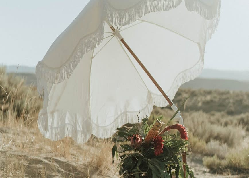 white umbrella and basket with flowers on sandy coast