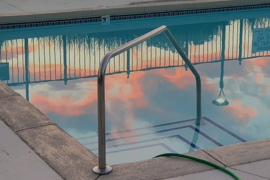pool with railing near hose and fence in hotel yard